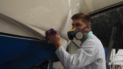 A young man (guy) is a specialist in cleaning the yacht, in a respirator and using a spray on the background of the yachts. Concept from: Professional, Specialist, Cleaning, Yacht service, Preparation