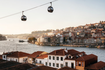 Old town of Porto on Douro River with cable cars and boats at sunset, Portugal.