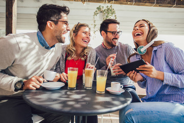 Group of four friends having fun a coffee together. Two women and two men at cafe talking laughing and using digital tablet.