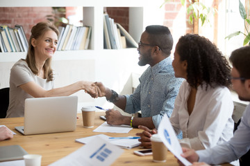 Smiling millennial businesswoman shake hand of African American male employee acquainting at meeting, happy female CEO handshake black worker greeting him at team or congratulating with work success