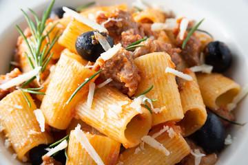 Piatto di mezze maniche con salsiccia, olive e formaggio