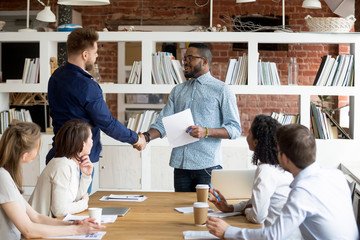 African American team leader or boss handshake Caucasian employee congratulating with work success, black manager shake hand of male worker greeting with high results and personal achievements
