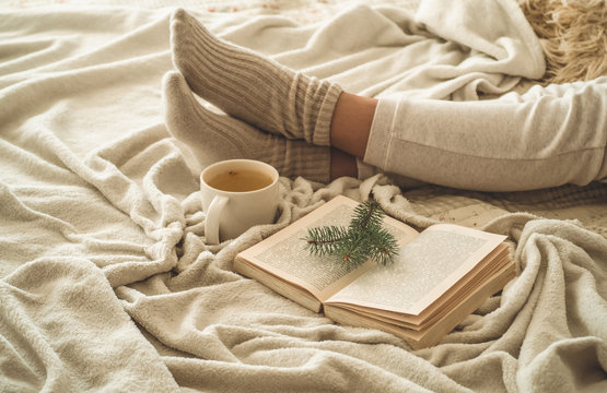 Cozy winter evening , warm woolen socks. Woman is lying feet up on white shaggy blanket and reading book. Cozy leisure scene