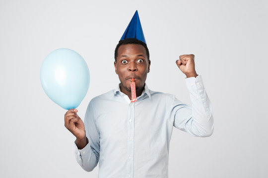 Young african man having fun on party wearing blue shirt and holiday hat, blowing party horn.