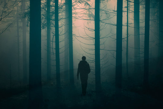 Man walking alone on foggy rural misty forest road. Double exposure used.