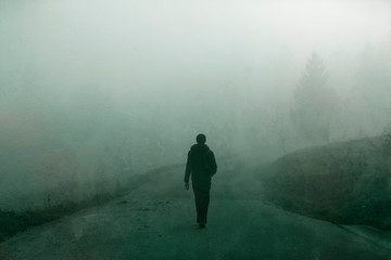 Man walking alone on grunge textured foggy rural road.