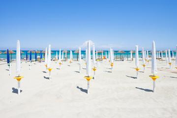 Alimini Grande, Apulia - Folded sunshades at the beautiful beach of Alimini Grande