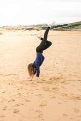 girl doing handstand in the sand