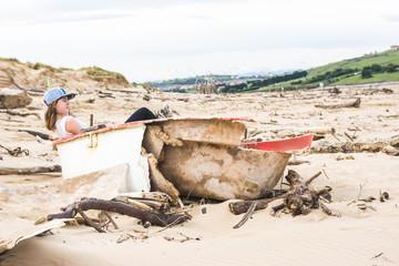 Teen girl sitting on broken boat on beach