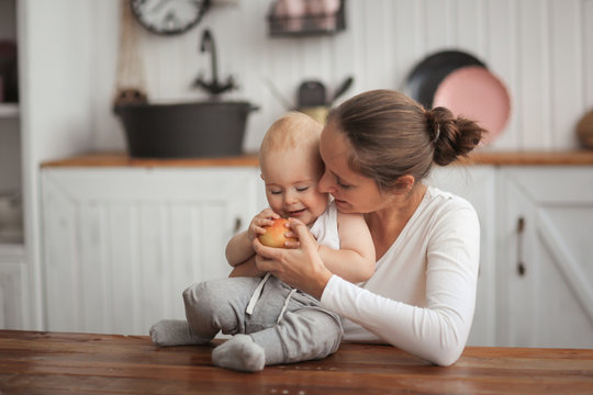 mother gives the baby apple, mother hugs son