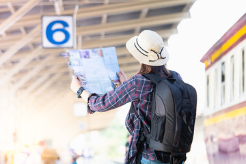 Woman tourist,traveler backpacker standing and looking the map at railway station with sun light blured background ,Travel summer and Lifestyle concept.