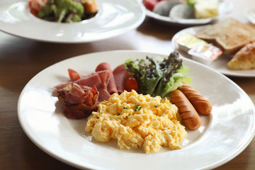 Breakfast scrambled egg with bacon sausage and salad on wood background
