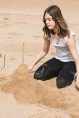 Teenager building sand castle