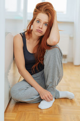 Young distressed woman sitting on floor at home