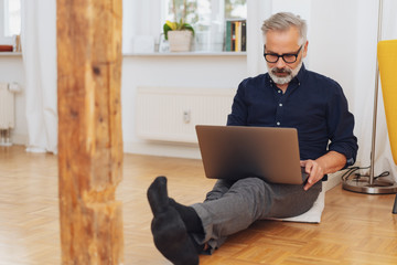 Man working on laptop while sitting on the floor