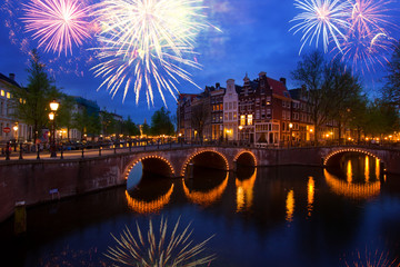 famous canals and bridgres of Amsterdam in night with fireworks, Netherlands
