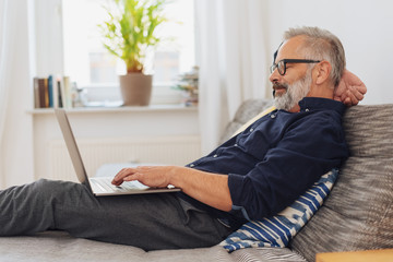 Businessman relaxing on a day bed using his laptop