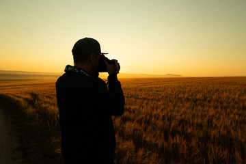 Man take a photo in sunrise in field
