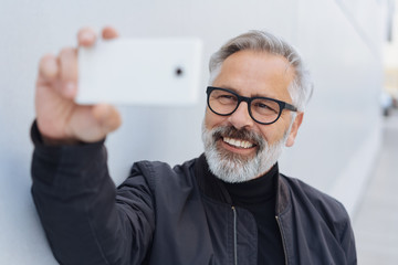 happy man posing for a selfie on his mobile