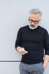 Trendy senior man standing looking at a mobile