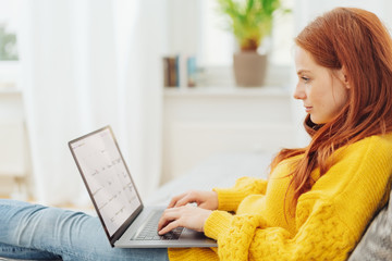 Young redhead woman using her laptop at home