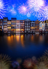 Houses facades over canal with reflections illuminated at blue night with fireworks, Amsterdam, Netherlands