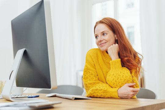Young cheerful woman sitting in front of computer