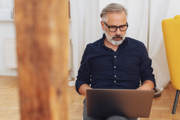 Middle-aged man working on laptop at home