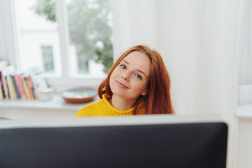Smiling ginger girl sitting in front of monitor