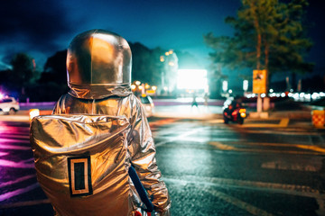 Rear view of spaceman on a street in the city at night attracted by shining projection screen