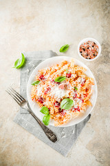 Italian food, fusilli pasta with  tomato sauce, grated parmesan cheese and basil, light stone table copy space top view