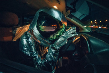 Spaceman sitting in car at night