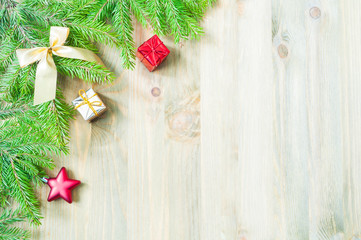 New Year and Christmas background. Christmas toys, blue fir tree branches on the wooden background