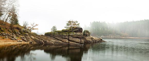 Fall season fog at beach with rock and trees. Herbstliche Nebellandschaft mit Felsen und Bäumen.