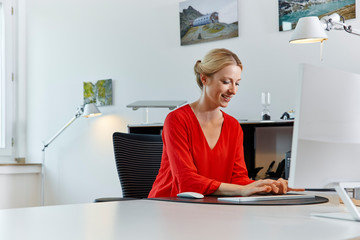 Smiling young woman working on computer at desk in office