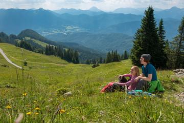 Germany, Bavaria, Brauneck near Lenggries, happy young couple having a break sitting in meadow in alpine landscape