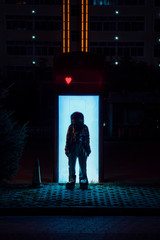 Spaceman standing at an illuminated box at night