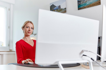 Portrait of young woman working on computer at desk in office