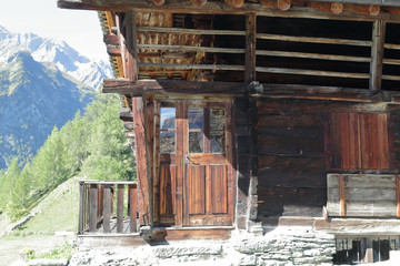 A typical German speaking Walser lodge, made of stone with board protected wooden balconies, in summer, in Val d'Otro valley, Alps mountains, Italy