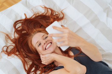 Smiling woman lying in bed with mobile phone