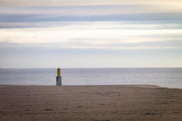 Beacon in the Sand Near the Ocean