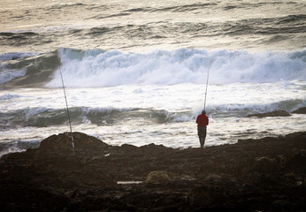Fisherman at the Rocky Shore