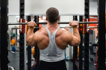 muscular man trains his shoulders with a barbell in the gym. Health and fitness concept