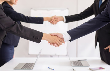 Business team people shaking hands finishing up meeting together in office room