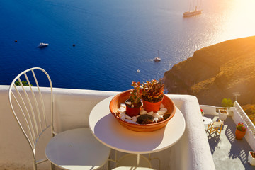 Table with flower pots on the terrace of Santorini, sunset sun, sea and ship in the background