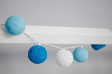 white and blue decoration balls, textile garland, cozy children's room concept