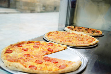 Showcase pizzeria with different types of pizza
