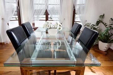 Obraz Szklany stół wraz z krzesłami w gościnnym pokoju - fototapety do salonu