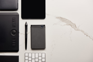 flat lay with graphics and digital tablet with portable hdd and wireless keyboard on white marble surface