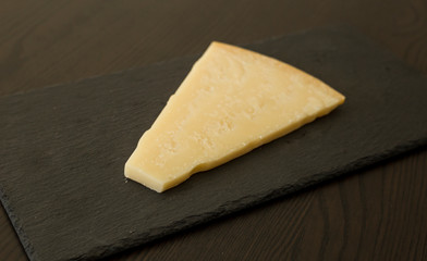 Slice of cheese on black slate board, close-up